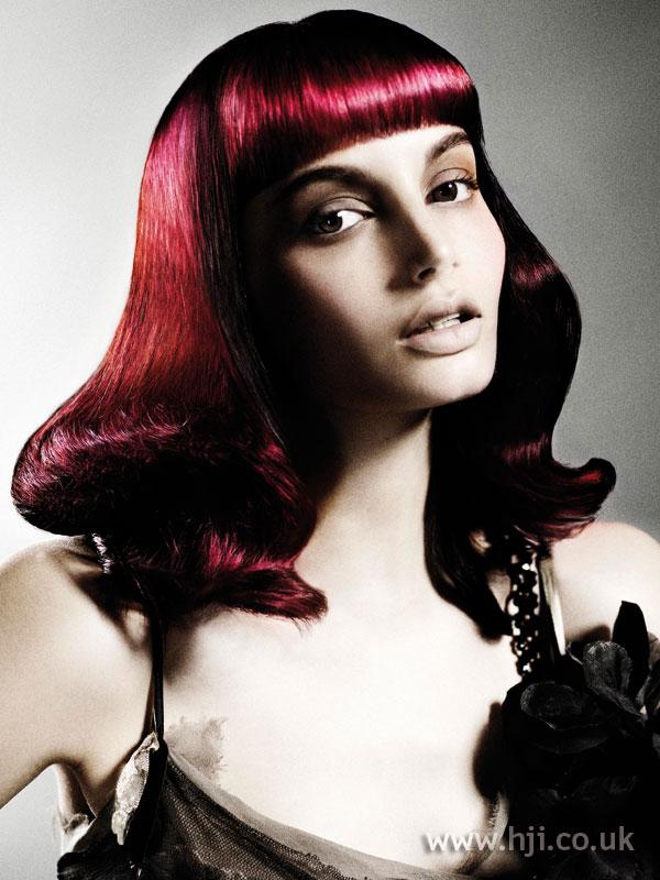 Tmavo červené vlasy.